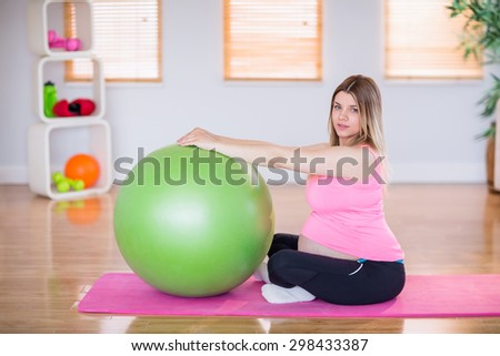 Pregnant woman doing exercise with exercise ball at home - stock photo