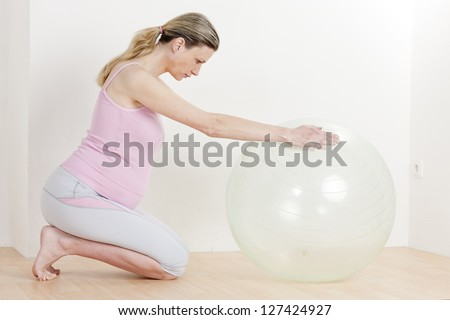 pregnant woman doing exercises with a ball - stock photo