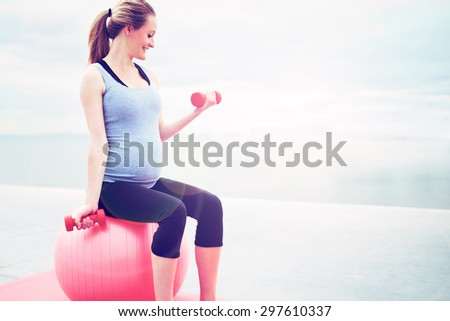 Pregnant woman doing fitness exercises sitting on a pilates gym ball working out with dumbbells, profile view with copyspace - stock photo
