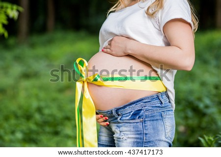 Pregnant woman embraces the stomach, tied with ribbon. Belly closeup - stock photo