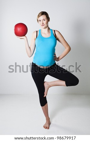 Pregnant woman exercising with a red exercise ball while balancing on one leg - stock photo