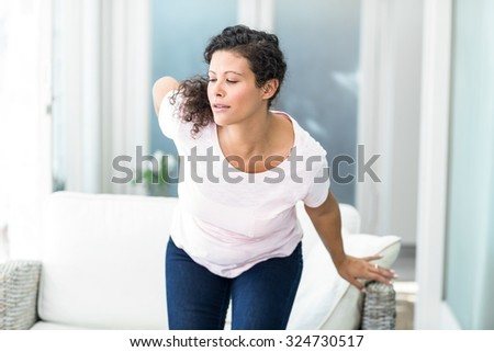 Pregnant woman getting up from sofa with hand on hip at home - stock photo