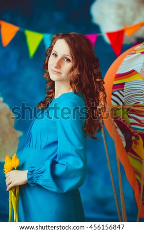 pregnant woman holding a yellow flowers - stock photo