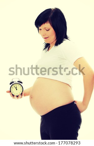 Pregnant woman holding alarm clock isolated in white - stock photo