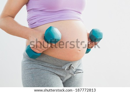 Pregnant woman holding dumbbells in a fitness studio - stock photo