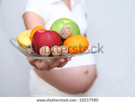 Pregnant woman holding fruits. Nine month. Third trimester - stock photo