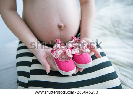 Pregnant woman holding pink baby shoe in her hand. Pregnant Woman Belly. Pregnancy - stock photo