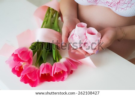 pregnant woman holding tiny pink child socks in hands with love. pregnancy. mother awaiting for childbirth. pregnant belly. family concept - stock photo