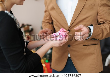 Pregnant woman holds pink booties. Beautiful pregnant woman and her husband in black dress and brown suit. Wife holds  two booties. - stock photo
