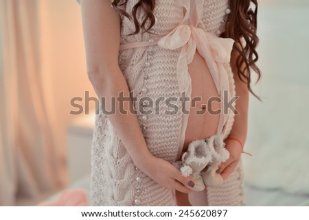 pregnant woman in a knitted jacket with a bow in his hands holding baby boots - stock photo