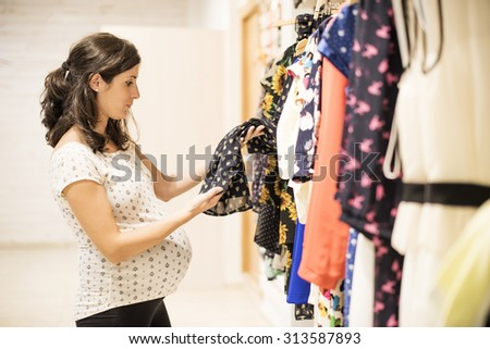 Pregnant woman in clothes store looking some clothes to buy - stock photo