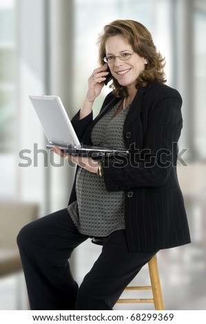 pregnant woman in her 40's, with laptop, phone, sitting in office - stock photo
