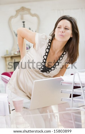Pregnant woman in home office with a sore back - stock photo
