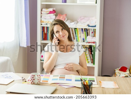 Pregnant woman in home office with mobile phone - stock photo