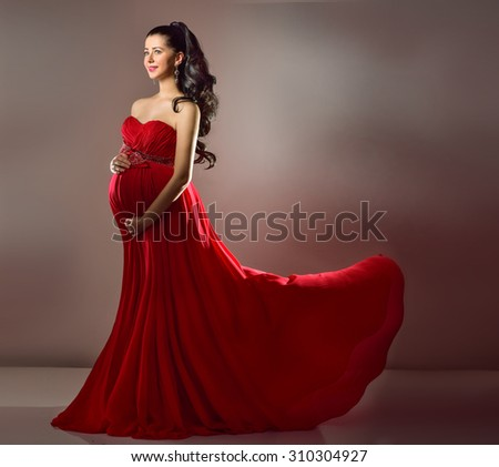 Pregnant woman in red evening dress flying on wind - stock photo