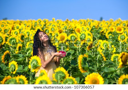 Pregnant woman in sunflowers - stock photo