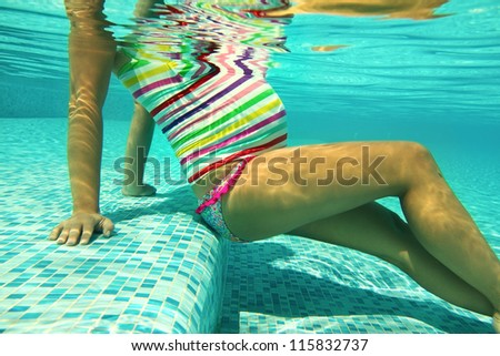 Pregnant woman in the pool in the bright striped swimsuit - stock photo