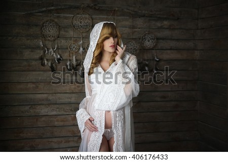 Pregnant woman in white dress in the shaman's house with dreamcatcher on the wall - stock photo