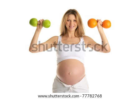 Pregnant woman involved in fitness dumbbells made from apples and oranges - stock photo