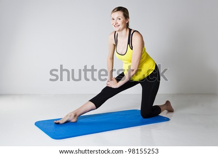 Pregnant woman kneeling on a mat and performing a hamstring muscle stretch of the leg - stock photo