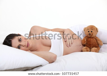 Pregnant woman laying on bed with teddy - stock photo