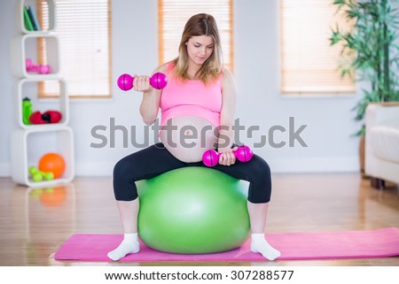 Pregnant woman lifting dumbbells on exercise ball in the living room - stock photo