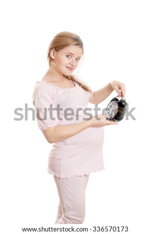 Pregnant woman looks at the clock on a white background - stock photo