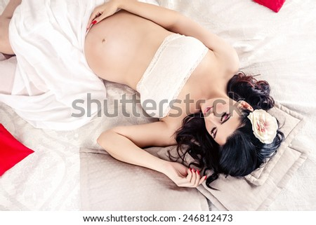 Pregnant woman lying on bed - stock photo