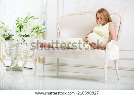 pregnant woman lying on couch at home  - stock photo