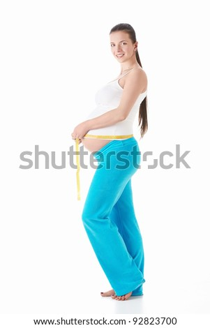 Pregnant woman measuring belly centimeter on a white background - stock photo