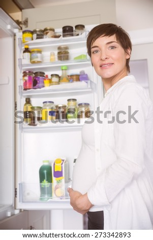 Pregnant woman opening the fridge at home in the kitchen - stock photo
