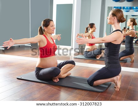 pregnant woman pilates exercise workout at gym with personal trainer - stock photo