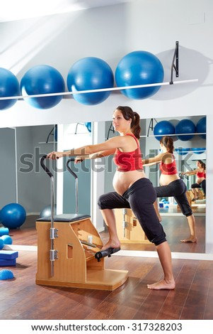 pregnant woman pilates exercise wunda chair at gym indoor - stock photo