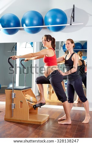 pregnant woman pilates exercise wunda chair at gym with personal trainer - stock photo