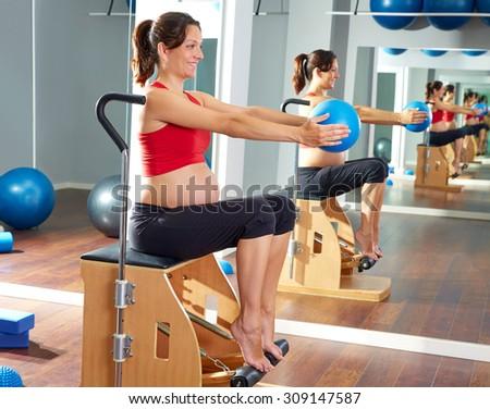 pregnant woman pilates leg pumps exercise on wunda chair - stock photo