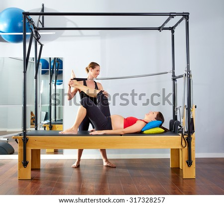 pregnant woman pilates reformer leg spring  exercise workout with personal trainer - stock photo