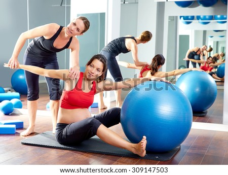 pregnant woman pilates saw exercise workout at gym with personal trainer - stock photo