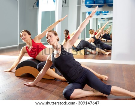 pregnant woman pilates side stretching exercise with Wave corrector and personal trainer - stock photo