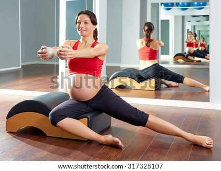 pregnant woman pilates side stretchs exercise with Wave corrector - stock photo