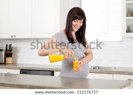 Pregnant woman pouring glass of orange juice in kitchen - stock photo