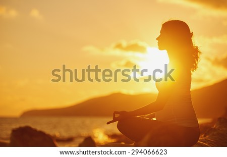 Pregnant woman practicing yoga, sitting in lotus position on a beach at sunset - stock photo