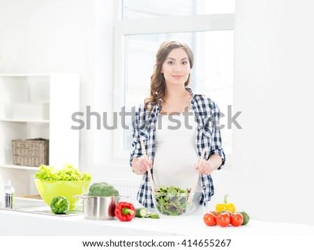 Pregnant woman preparing dieting food at kitchen. - stock photo