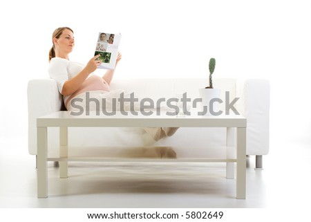Pregnant woman reading a magazine on a couch. - stock photo