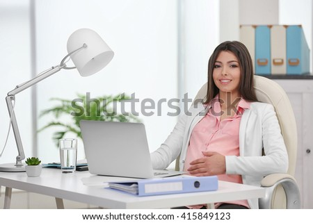 Pregnant woman sitting at her workplace in the office - stock photo