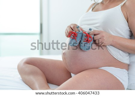pregnant woman sitting bed holding baby shoes - stock photo
