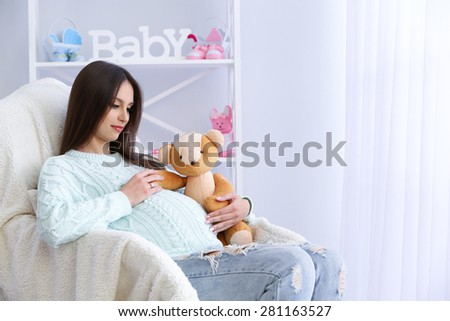 Pregnant woman sitting in armchair, indoors - stock photo