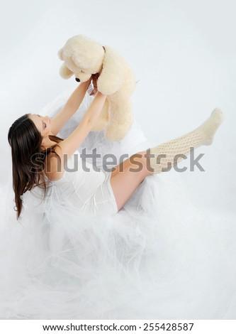 Pregnant woman sitting near teddy bear - stock photo