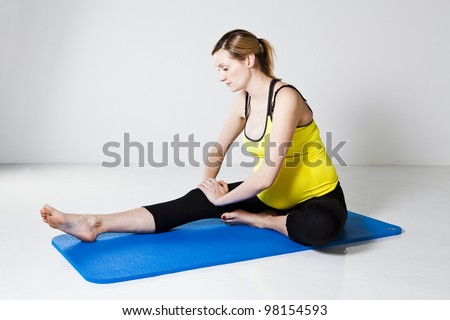 Pregnant woman sitting on a mat and performing a hamstring muscle stretch of the leg - stock photo
