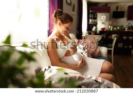 pregnant woman sitting on sofa, Image of pregnant woman touching her belly with hands, relaxing at home on the couch, pregnant mother keeping her hands on belly while looking at it - stock photo
