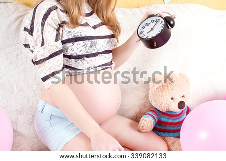 Pregnant woman sitting on the couch with alarm - stock photo